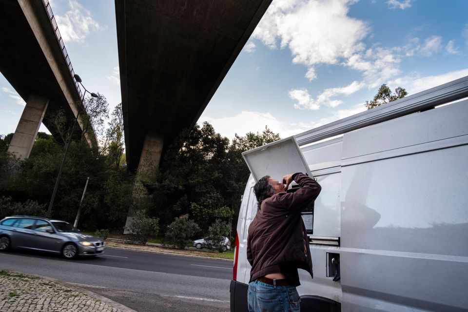 A man takes a dose of methadone from a van that provides it to combat drug addiction in Lisbon, Portugal...