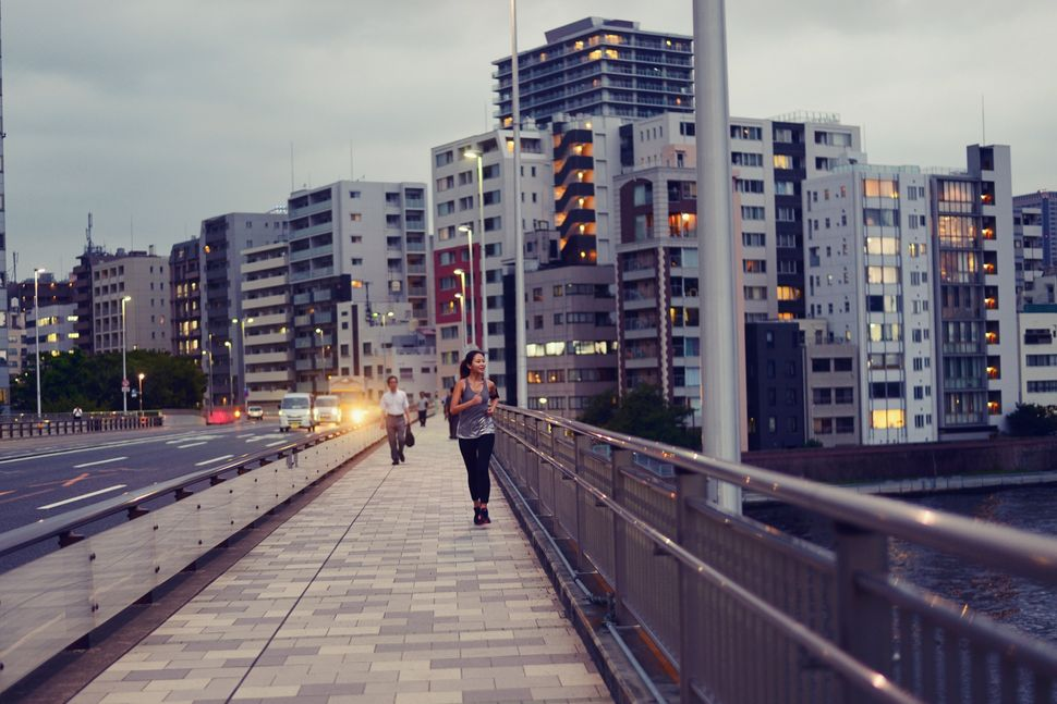 Μια γυναίκα τρέχει μέσα στην πόλη.