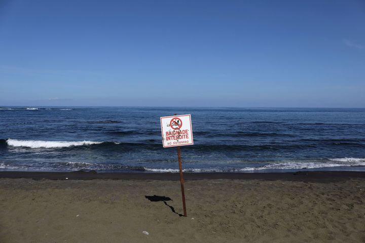 A picture taken on March 1, 2019, shows a sign banning swimming at the L'Étang-Salé beach, on the Indian Ocean
