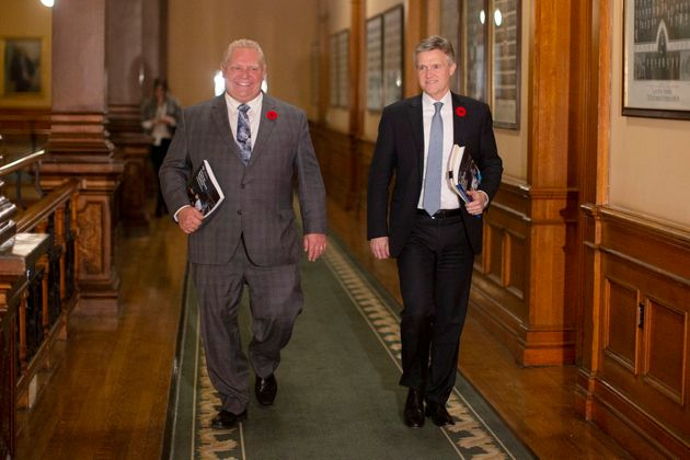 Ontario Premier Doug Ford and Finance Minister Rod Phillips walk to the legislative chamber to deliver...