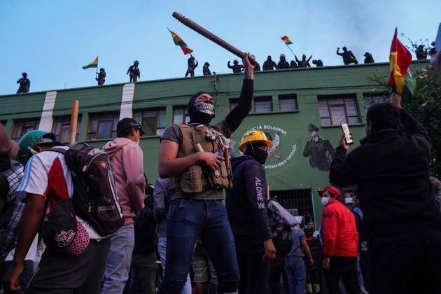 Des manifestants soutiennent les policiers sur le toit de leur quartier général à...