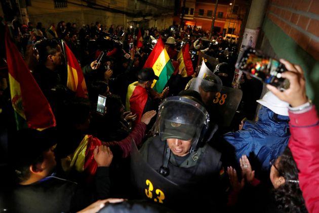 Des manifestants applaudissent des policiers antiémeute à La Paz, ce 8