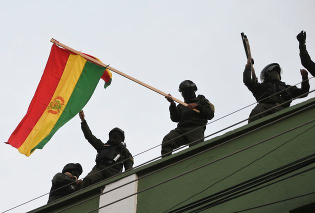 Police officers wave a national flag while standing on the roof of their headquarters, in Cochabamba,...
