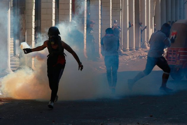 An anti-government protester prepares to throw a tear gas canister fired by Iraq security forces during...