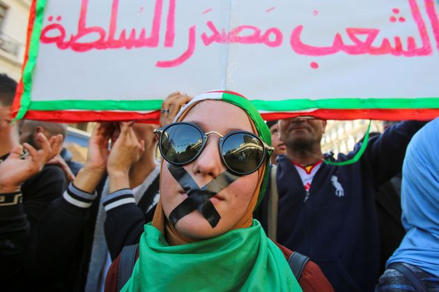 A demonstrator with tapes over her mouth takes part in a protest against the country's ruling elite and...