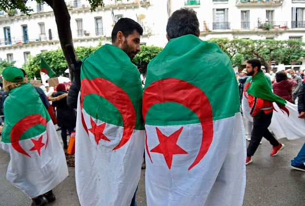 Algerian protesters, draped in their national flag, rally in the centre of the capital Algiers as anti-government...