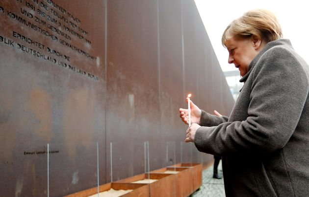 German Chancellor Angela Merkel lights a candle at the memorial of the divided city and the victims of...