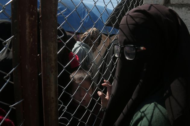 A woman looks through a chain linked fence at al-Hol displacement camp in Hasaka governorate, Syria March...