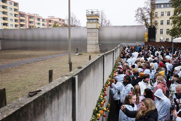 Des gens ont déposé des fleurs dans les vestiges du mur de Berlin lors d'une cérémonie...