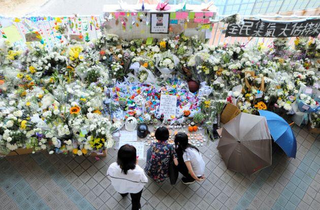 亡くなった大学生が転落した現場に花束やキャンドルを捧げる市民たち=2019年11月9日午後0時49分、香港・将軍澳、西本秀撮影