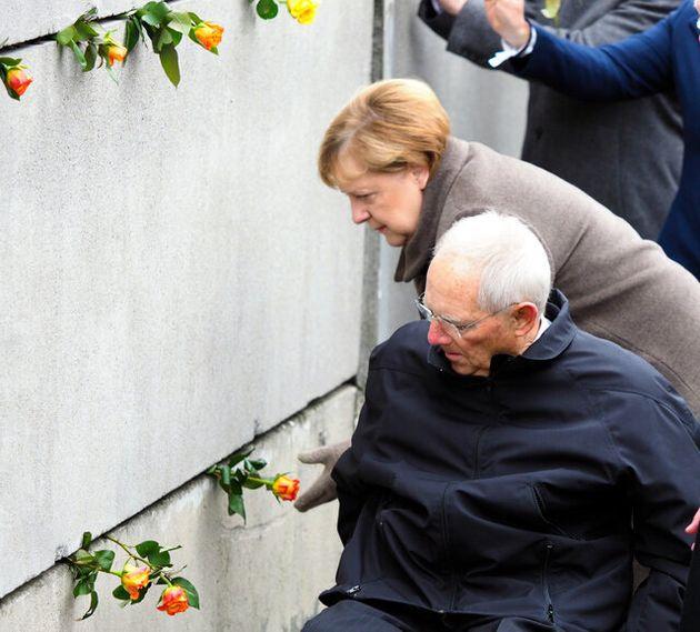 ベルリンの壁崩壊から30周年の式典で、壁の隙間にバラの花を挿すドイツのメルケル首相(奥)=2019年11月9日午前11時6分、ベルリン、野島淳撮影