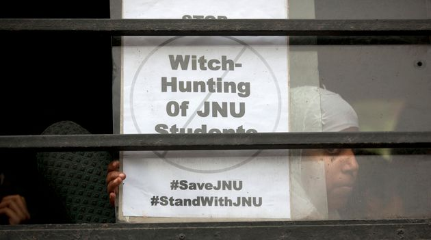 File photo of a student carrying a poster as she sits in a bus to join other protesters at the Jawaharlal...