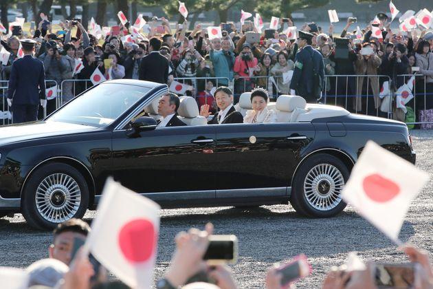 即位を祝うパレードで、沿道に集まった大勢の人々に手を振られる天皇、皇后両陛下=10日午後、皇居前広場