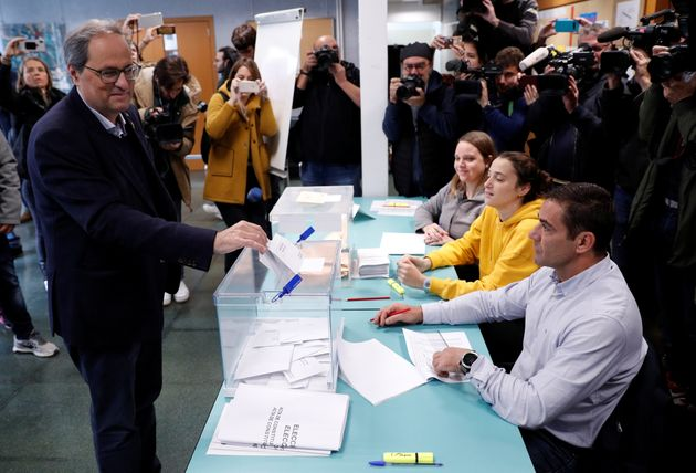 Catalan leader Quim Torra casts his vote as his daughter Helena Torra (wearing yellow) works at the polling...