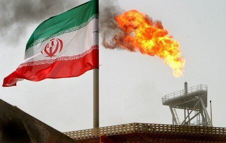 A gas flare on an oil production platform in the Soroush oil fields is seen alongside an Iranian flag...
