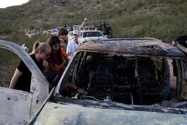 Relatives of slain members of Mexican-American families belonging to Mormon communities observe the burnt...