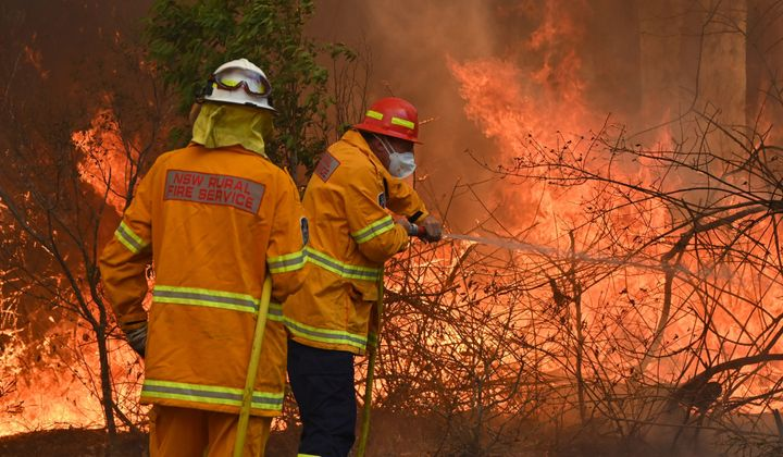Firefighters tackle a bushfire to save a home in Taree, NSW on Saturday.