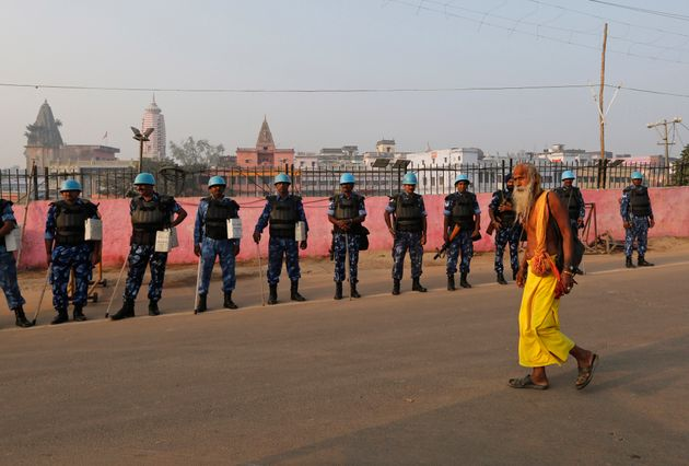 A sadhu walks past security officers standing guard in Ayodhya, Saturday, Nov. 9,