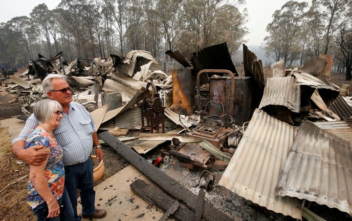 Lyn and Peter Iverson with their burnt out office and shed on their property at Half Chain road, Koorainghat.