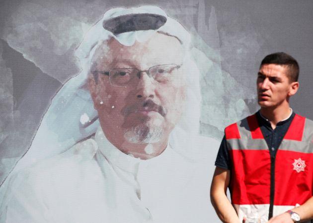 A Turkish police officer walks past a picture of slain Saudi journalist Jamal Khashoggi, near the Saudi...