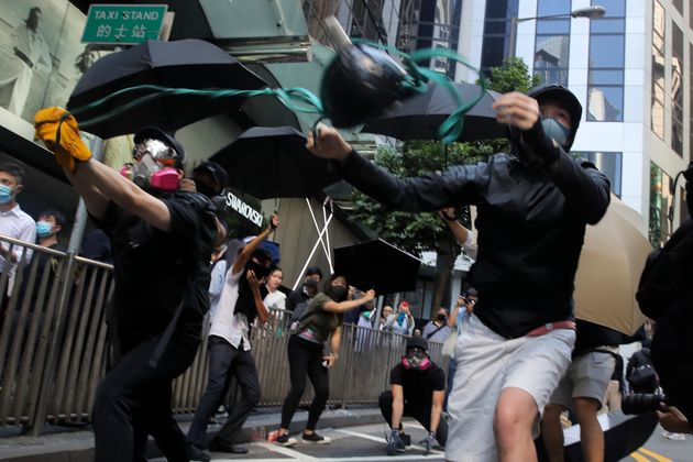 Protesters use a sling shot to launch a milk drink container towards riot police during protests in the...