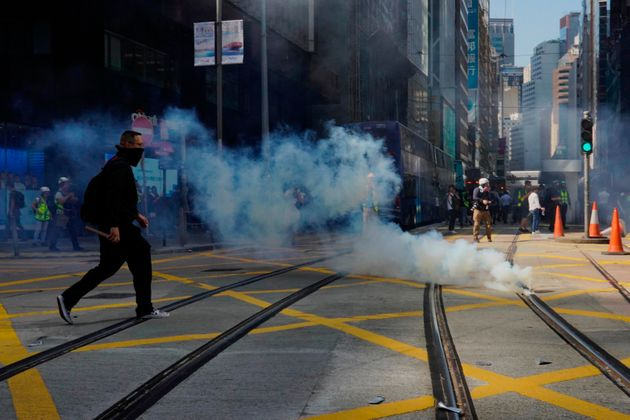 A protester approaches a gas canister deployed in Central district of Hong Kong on Monday, Nov. 11, 2019....