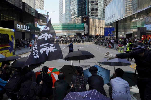 Protesters with umbrellas face off riot police in Hong Kong on Monday, Nov. 11, 2019. A protester was...