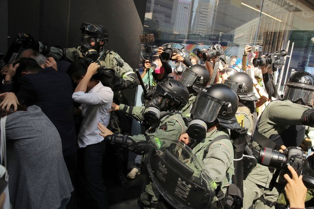 Riot police push a crowd to clear the area in Hong Kong on Monday, Nov. 11, 2019. A protester was shot...