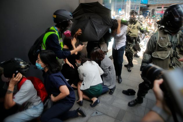A crowd tries to take cover from pepper spray in Hong Kong on Monday, Nov. 11, 2019. A protester was...