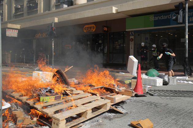 Protesters burn debris to block traffic in Hong Kong on Monday, Nov. 11, 2019. A Hong Kong protester...
