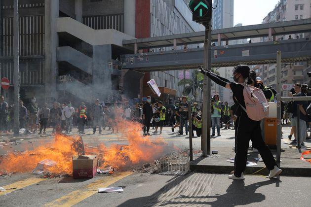 Protesters burn debris to block a road in Hong Kong on Monday, Nov. 11, 2019. Police in Hong Kong shot...
