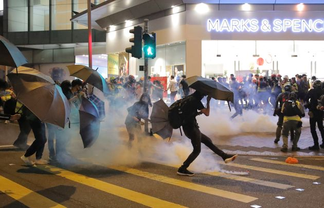 A protestor kicks away a police teargas shell as they clash outside a shopping mall in Hong Kong, Sunday,...