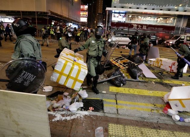 Riot police officers clear up a road from barricade set up by protesters in Mong Kok, Hong Kong, Sunday,...