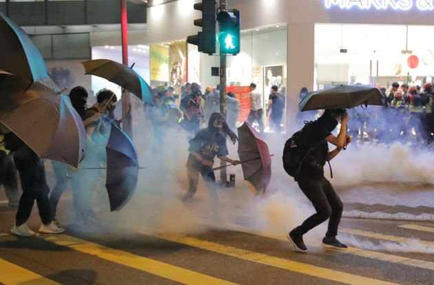 Protesters use umbrellas to protect themselves as they face police teargas in Hong Kong, Sunday, Nov....