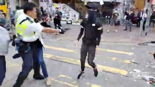 In this image made from video, a police officer, left, prepares to shoot a protester, center, in Hong...