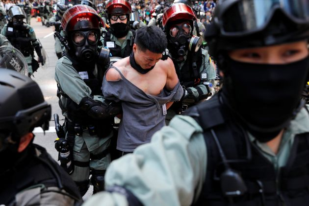Riot police detain an anti-government protester Monday in Hong