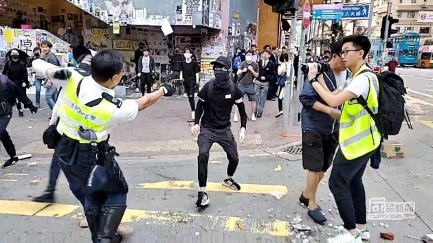 A screenshot from a video posted on social media shows a police officer aiming his gun at a protester...