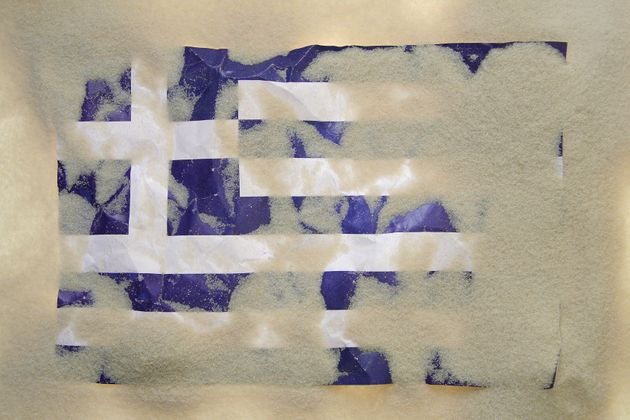 greek flag covered with sand
