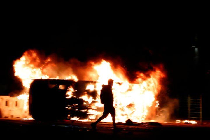An anti-government protester walks past a burning vehicle during a protest in Tseung Kwan O, Hong Kong, China November 11, 20