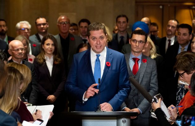 Conservative Leader Andrew Scheer is surrounded by members of his caucus as he speaks to reporters following...