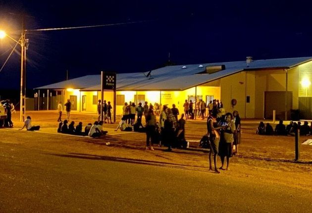 Yuendumu community members gather peacefully outside the police station after the fatal shooting of 19-year-old...
