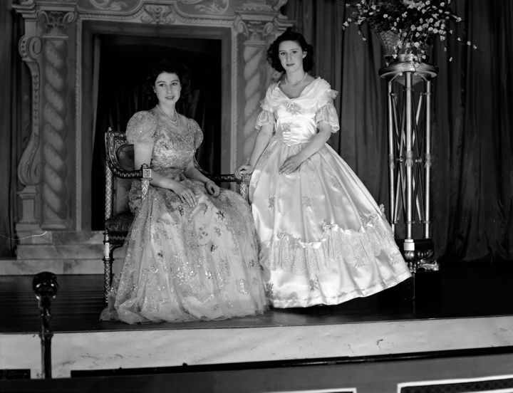 "Princesses Margaret and the future Queen Elizabeth wearing elaborate dresses for ""Old Mother Red Riding Boots,"" a Christmas pantomime they performed in at Windsor Castle."