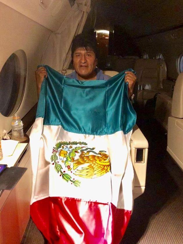 El expresidente de Bolivia Evo Morales mientras posa con una bandera mexicana, durante su viaje en un...