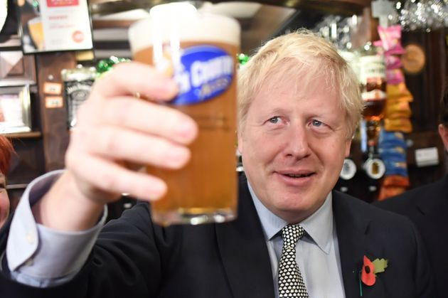 Prime Minister Boris Johnson, raises a pint as he meets with military veterans at the Lych Gate Tavern...