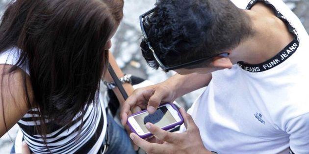 Dos jóvenes utilizando el teléfono