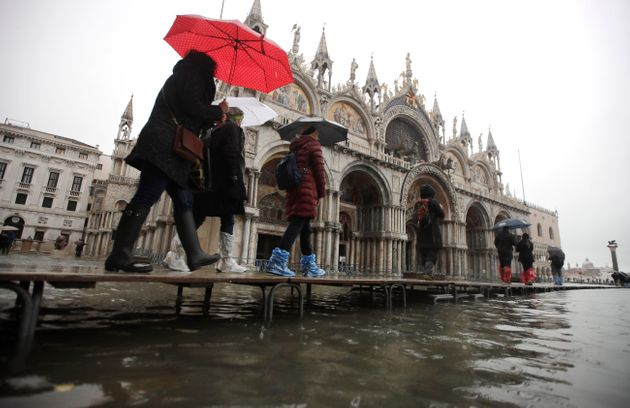 People walk on catwalk set up in front of St. Mark's Basilica on the occasion of a high tide, in a flooded...