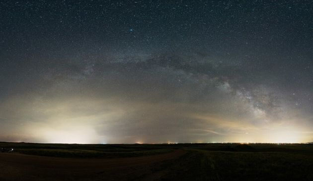 Seen from miles away, bright domes of light are cast upward from Fort Collins, Colorado, to the right...