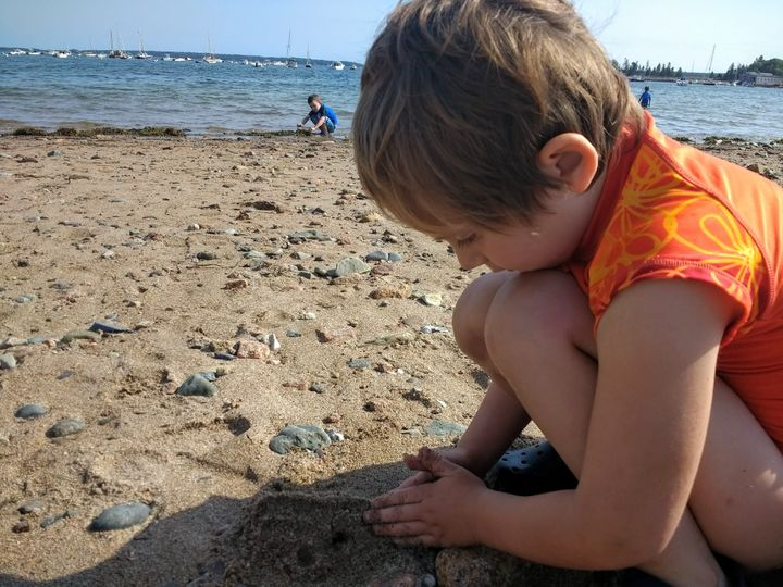 Alyssa Walker's daughter builds a sandcastle in the foreground with her son in the background.