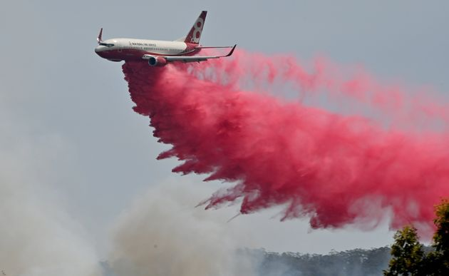 Rural NSW Fire Service plane drops fire retardent on an out of control bushfire near Taree, 350km north...