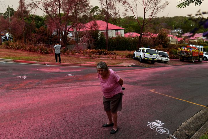 A resident walks infront of South Turramurra homes which were bombed by fire-retardant during NSW RFS firefighting efforts in Sydney.